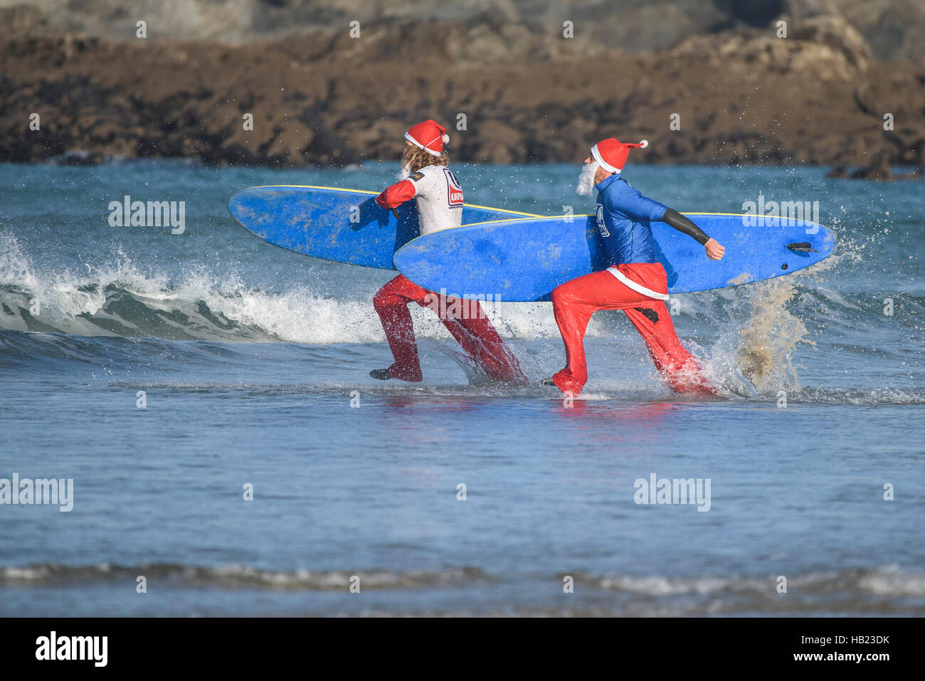 Newquay, UK. 04th Dec, 2016. Fistral Beach; Newquay, Cornwall. 4th December, 2016. Surfing Santas race into the - Stock Image
