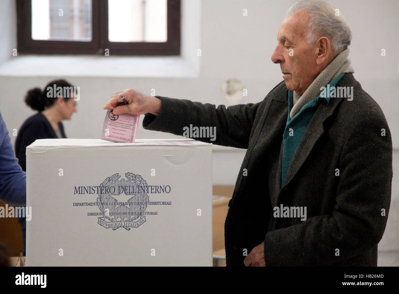 A voter votes at the polling station as others wait to enter during the referendum on constitutional reform - Stock Image