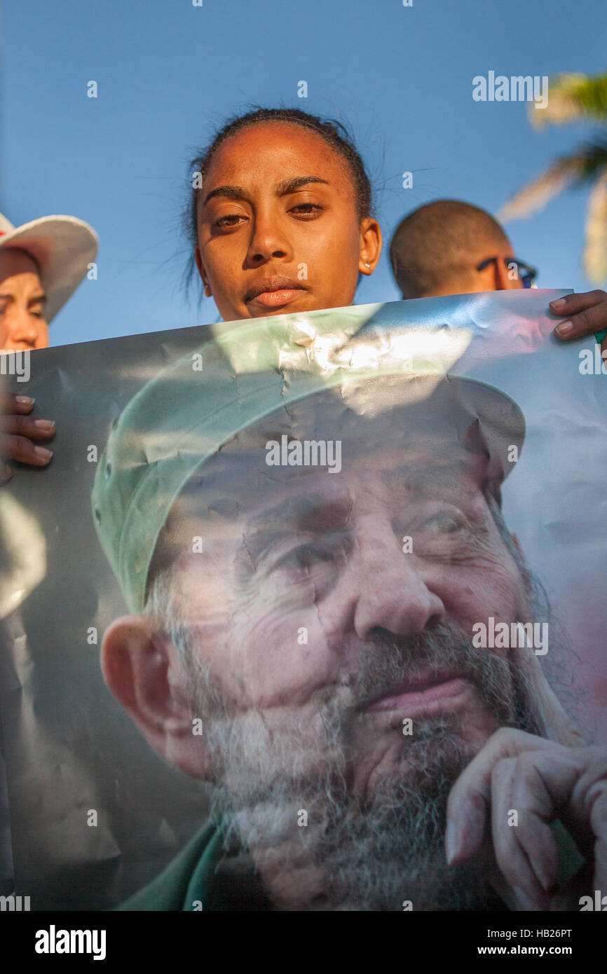 Santiago De Cuba, Cuba. 04th Dec, 2016.  A girl is holding a poster with a photograph of Fidel Castro on one of - Stock Image