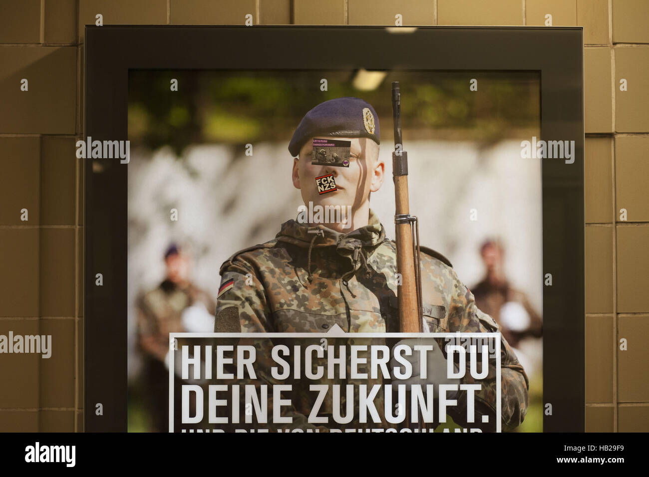 Berlin, Germany. 4th Dec, 2016. Stickers cover the face of a German soldier portrayed on a military draft poster, - Stock Image