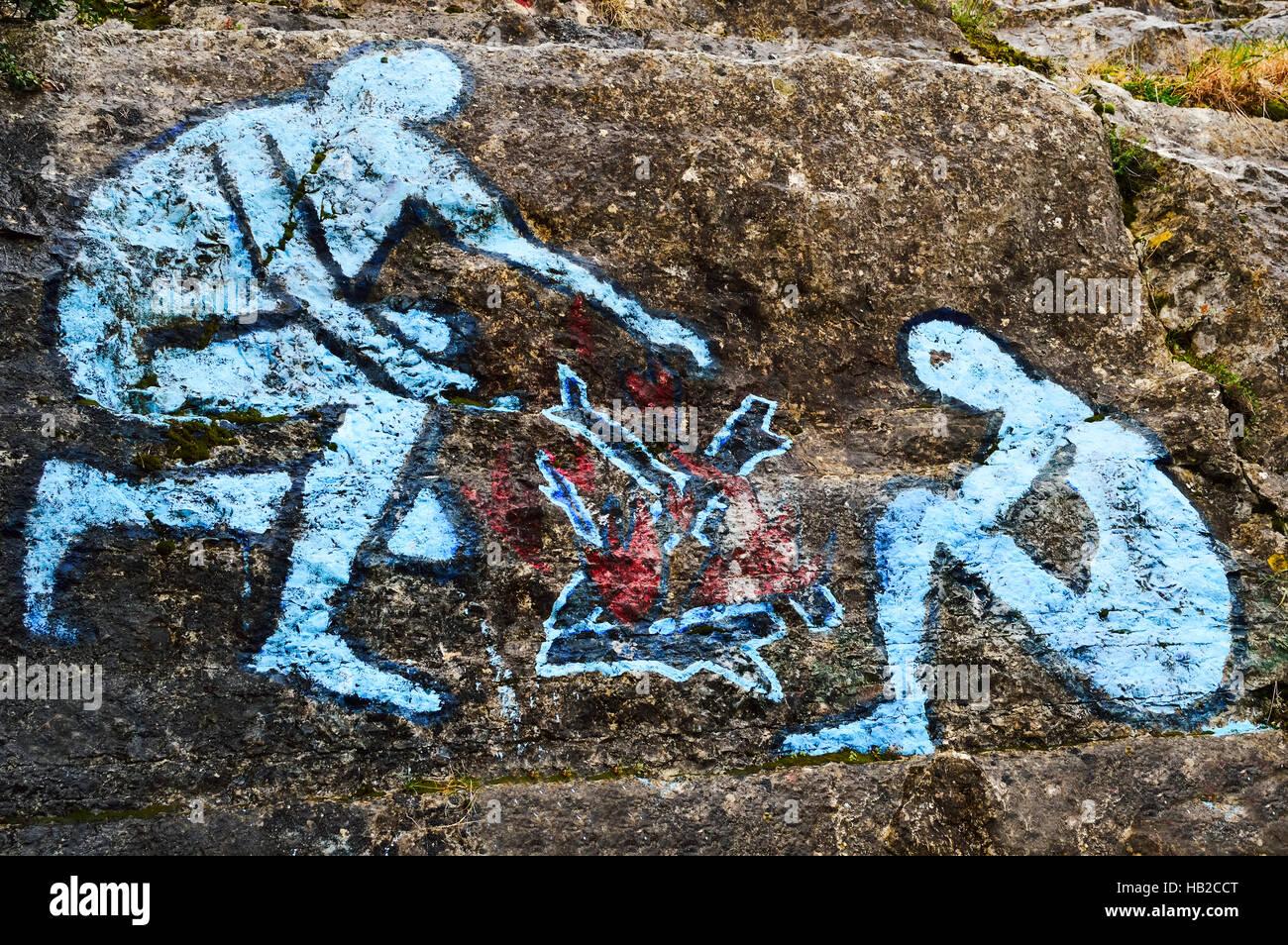 Graffiti man on fire on rock wall - Stock Image