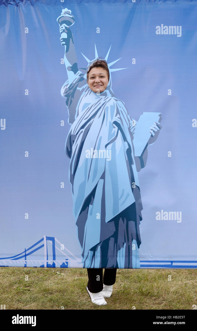 Humorous photo of a smiling woman being photographed in painted Statue of Liberty posing photo board - Stock Image