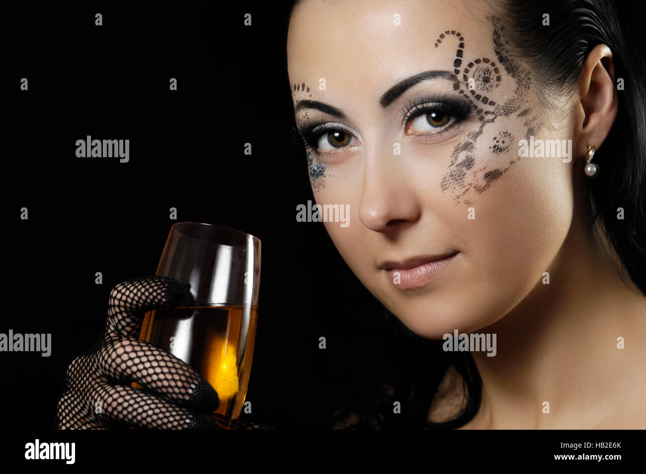 Beautiful woman with a romantic expression and creatively stencilled make-up holding a glass of wine - Stock Image