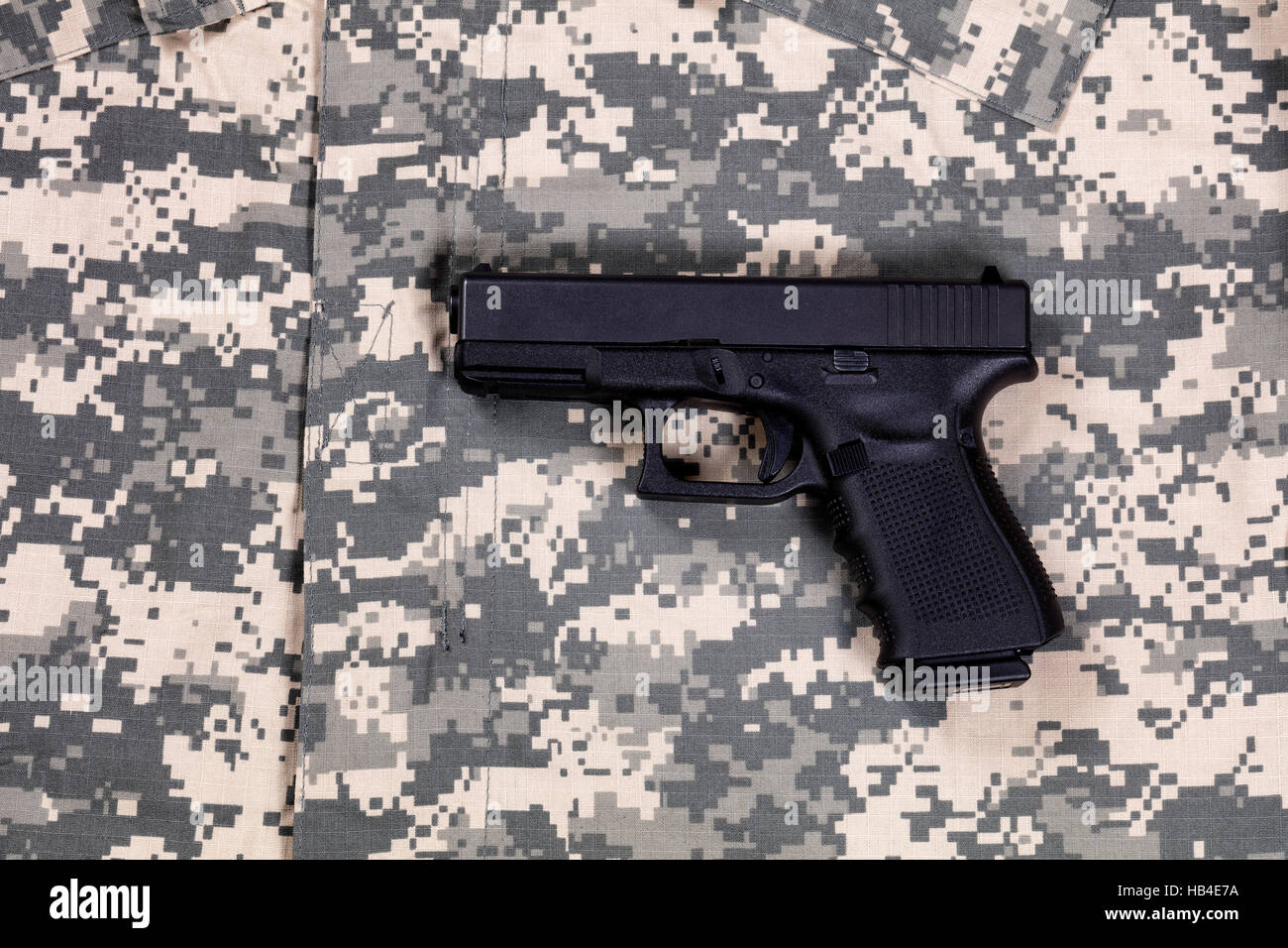 Camouflage battle dress uniform with weapon - Stock Image