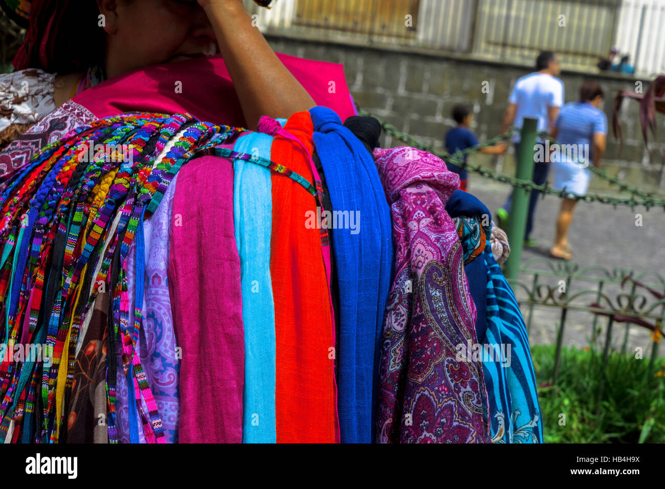 Colourful handmade scarves and beads on the arm of a Guatemalan woman closeup - Stock Image