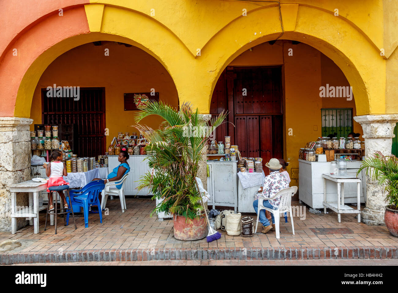 Locals sit by the store set out under the arches of a yellow building Cartagena, Colombia - Stock Image