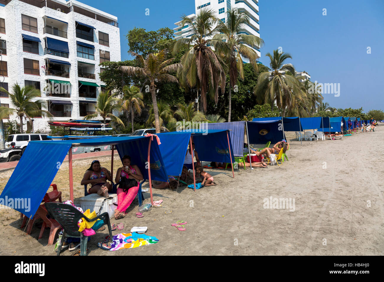 Families sitting in their beach tents on the Plaza Playa de Castillo Grande, Cartagena, Colombia - Stock Image