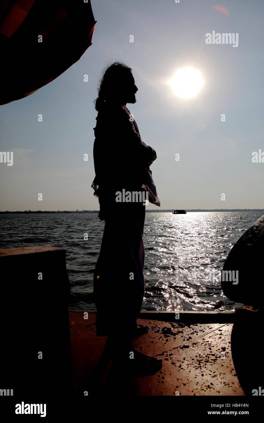 Silhouette of an Indian guru on a houseboat at sunset,Kerala,India. - Stock Image
