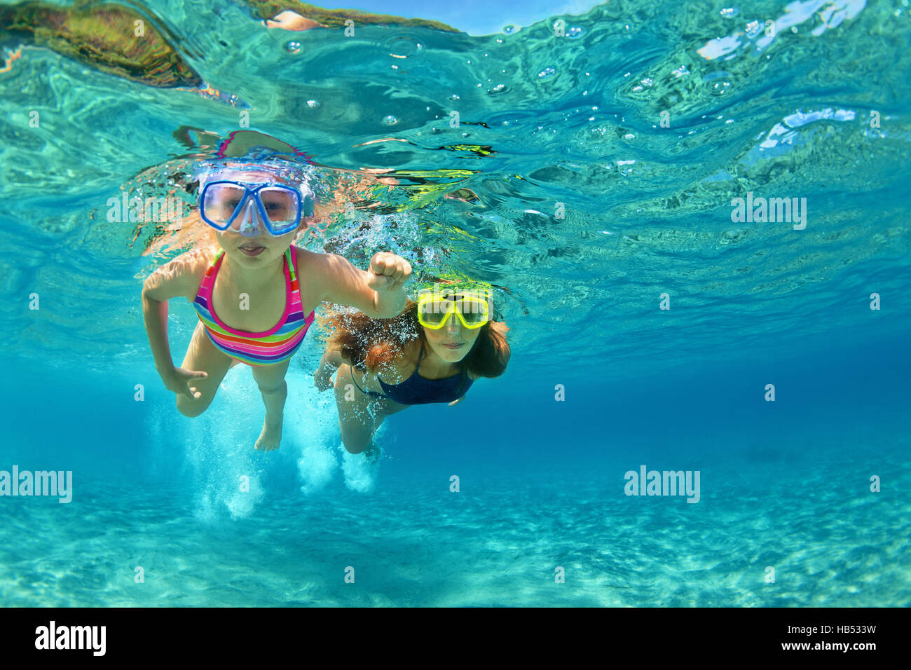 Happy family - mother with baby girl swim and dive underwater with fun in sea beach. Active parent, people water - Stock Image