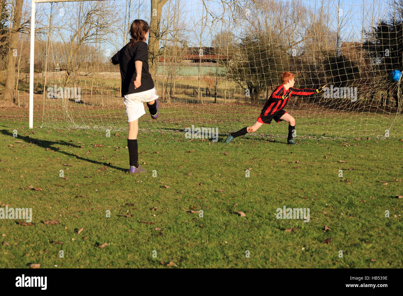 Girl taking penalty kick, English football - Stock Image