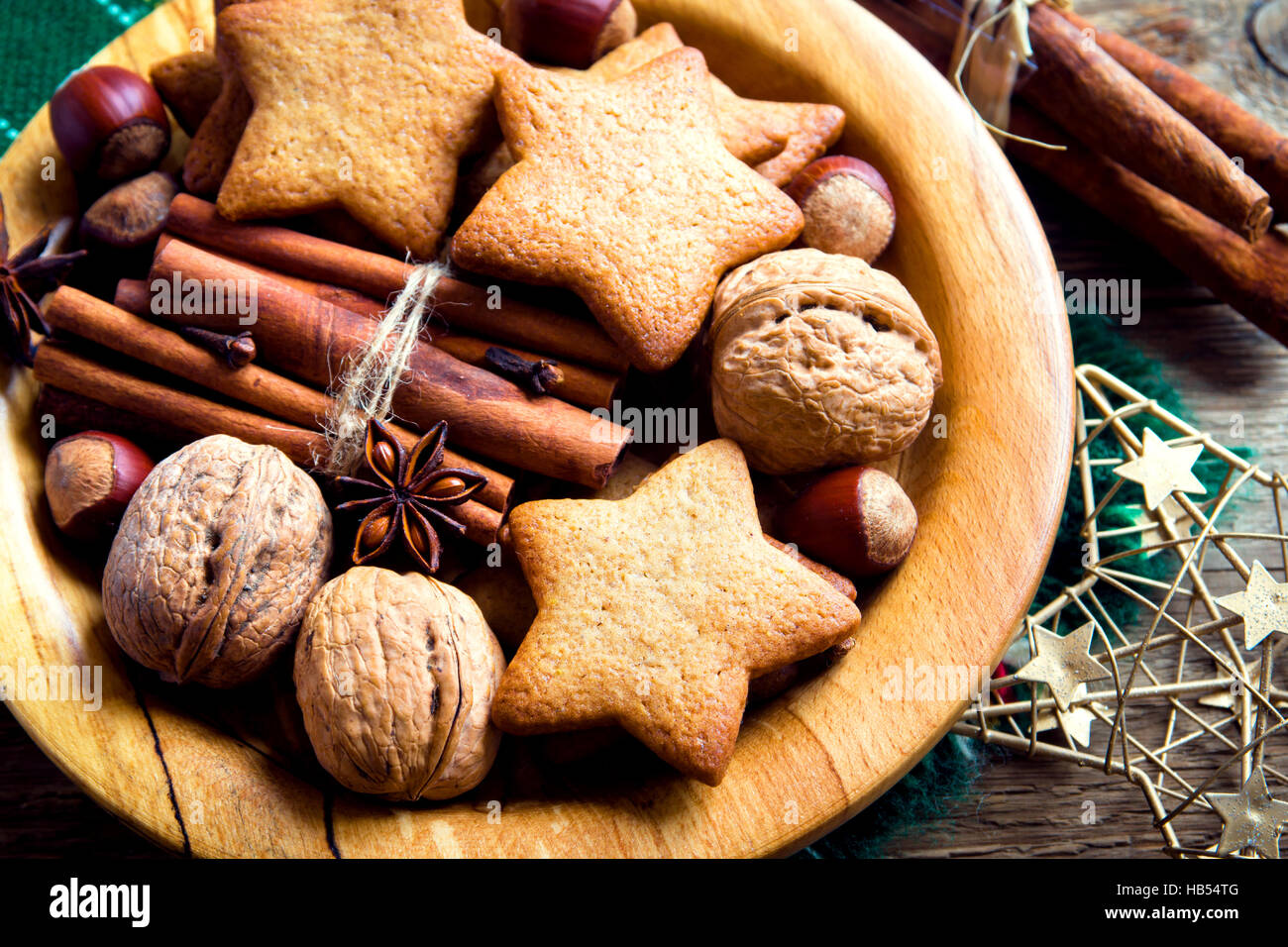 Rustic Christmas decoration with gingerbread cookies, nuts and Christmas spices on wooden plate close up - Stock Image