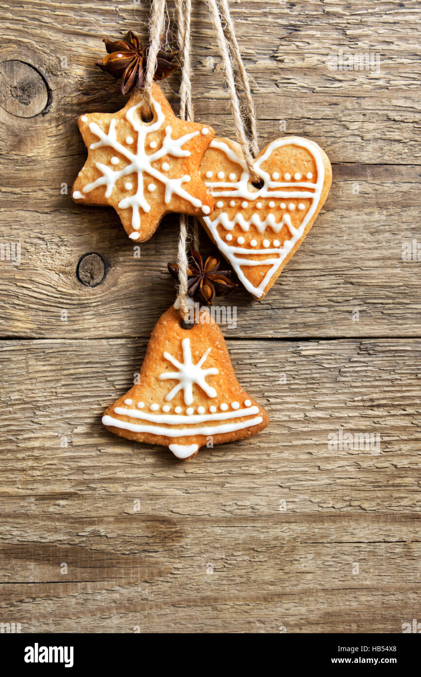 Gingerbread Christmas cookies hanging over wooden background with copy space - festive Christmas pastry and decor, - Stock Image