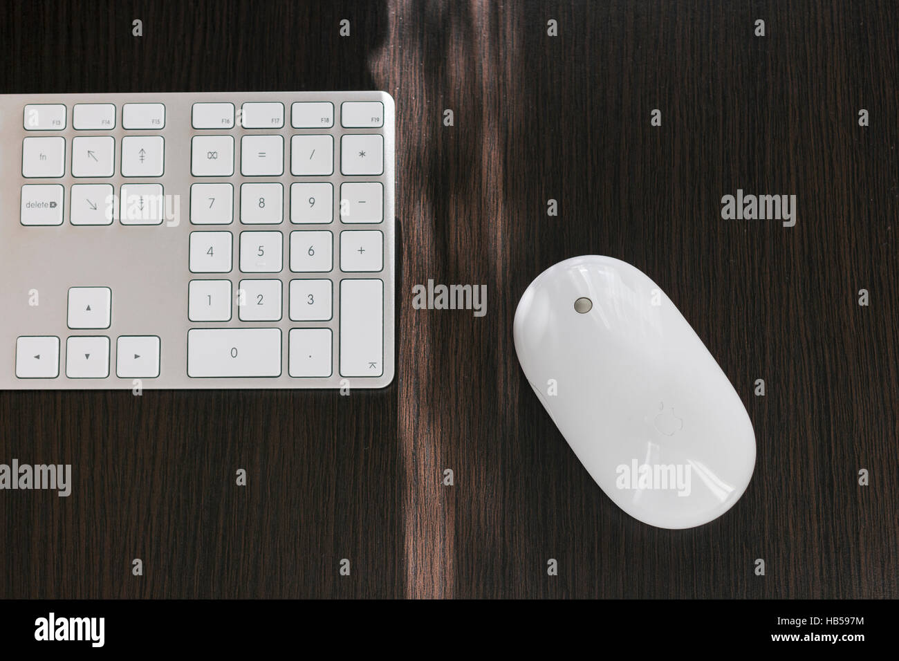 Apple mighty mouse on the dark desk next to the white keyboard - Stock Image
