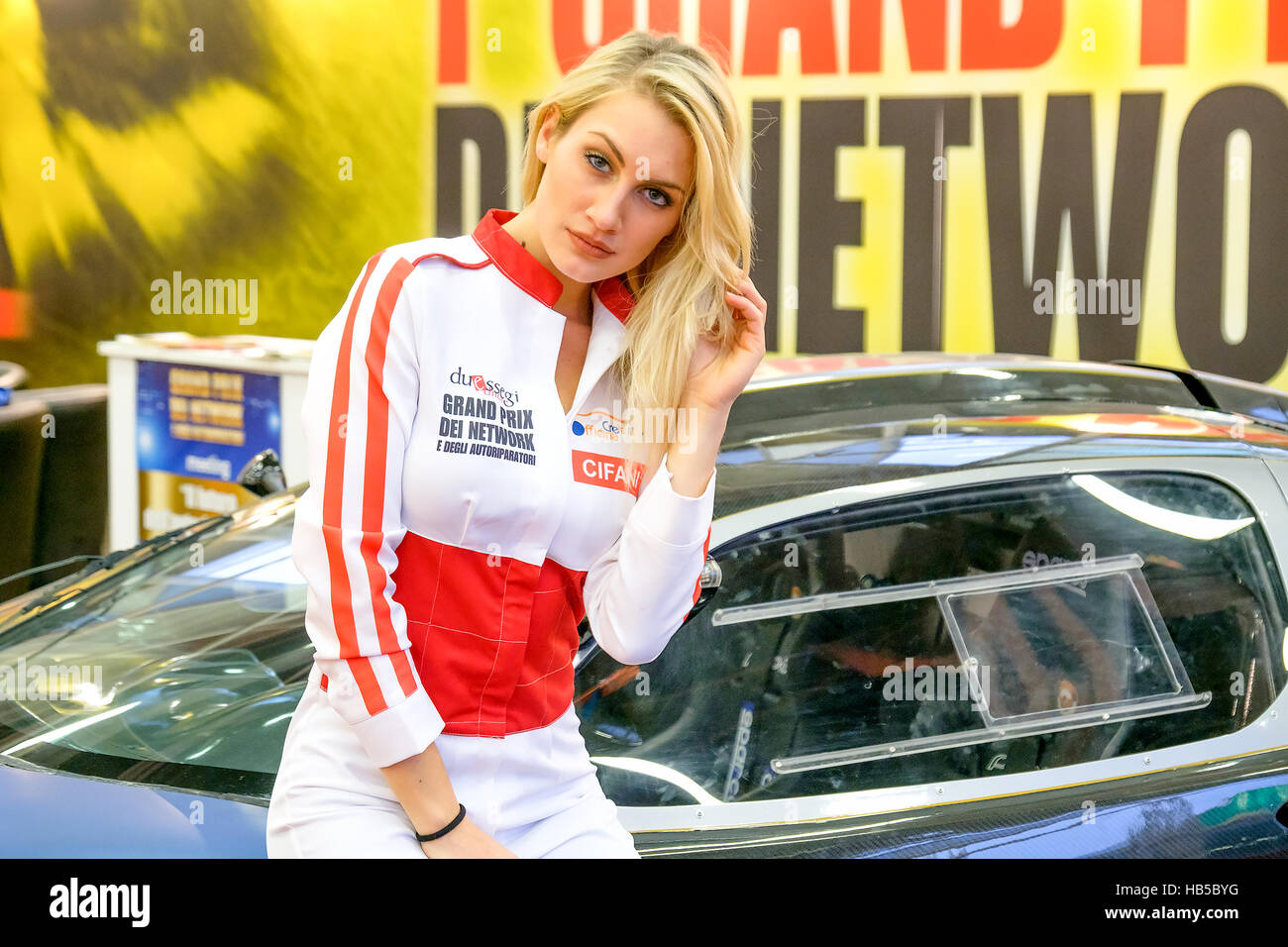 Bologna, Italy, Dec 03 2016 - a blonde model posing at the Motorshow 2016 in Bologna leaning to a sport car dressed - Stock Image