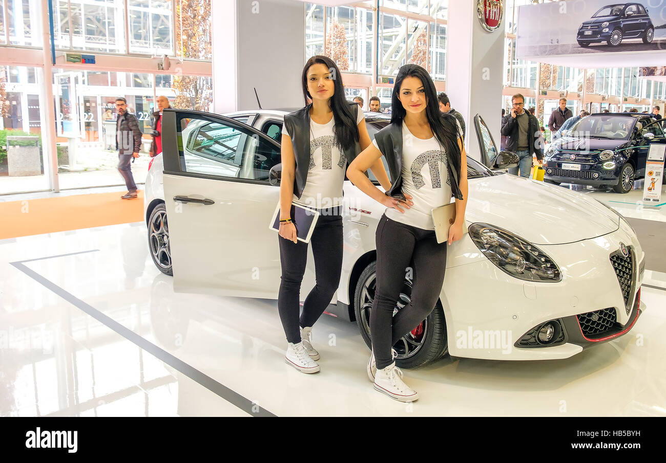 Bologna, Italy, Dec 03 2016 - two brunette models posing leaning to an white Alfa Romeo Giulietta car in the Fiat - Stock Image