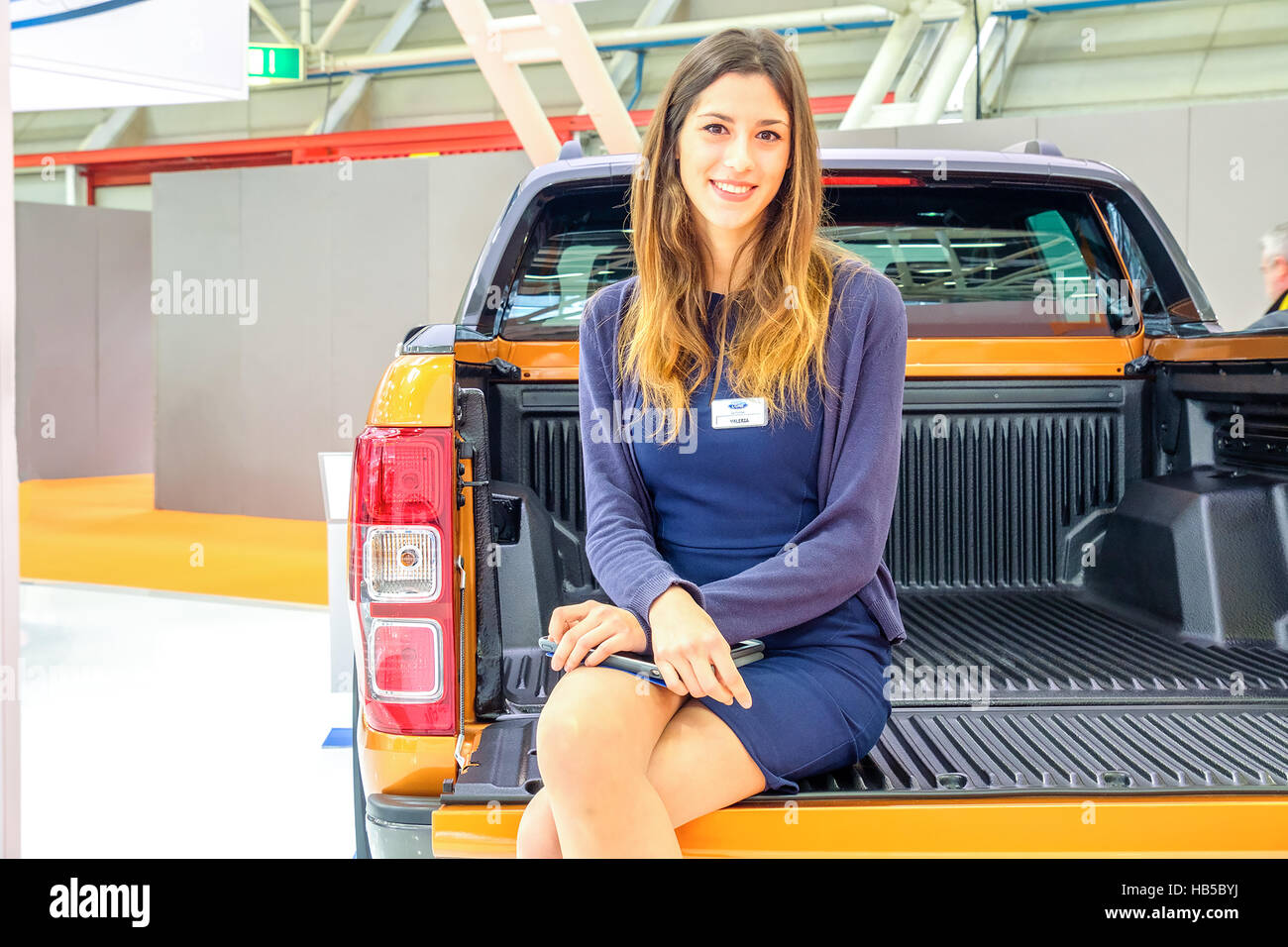 Bologna, Italy, Dec 03 2016 - a model sit in the back of an orange  Ford Ranger Wildtruck pickup during the Motorshow - Stock Image