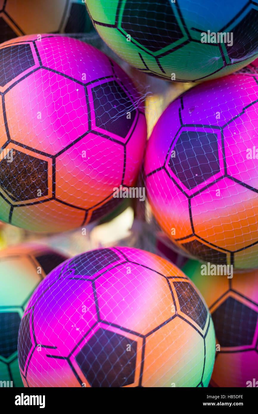 Multi-coloured footballs in a plastic mesh net. - Stock Image
