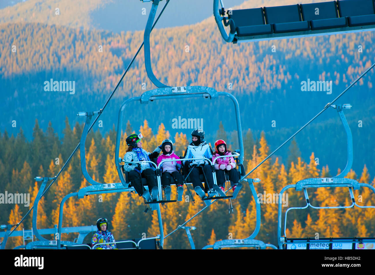 Women with children on a ski lift in Bukovel. Bukovel is the most popular ski resort in Ukraine. - Stock Image