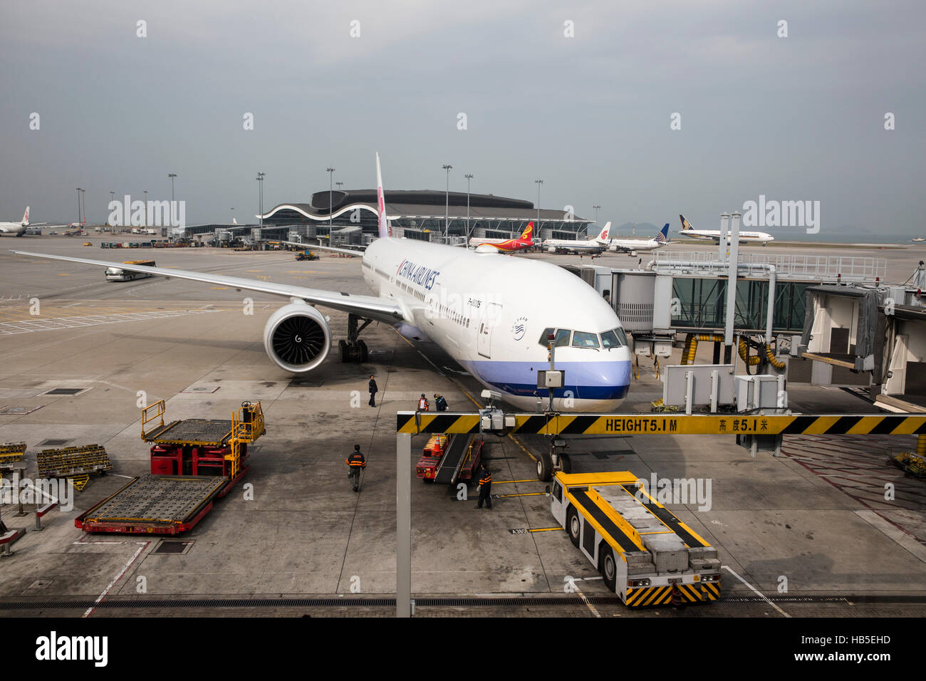 A airplane is being loaded with cargo in preparation for departure at Hongkong International Airport - Stock Image