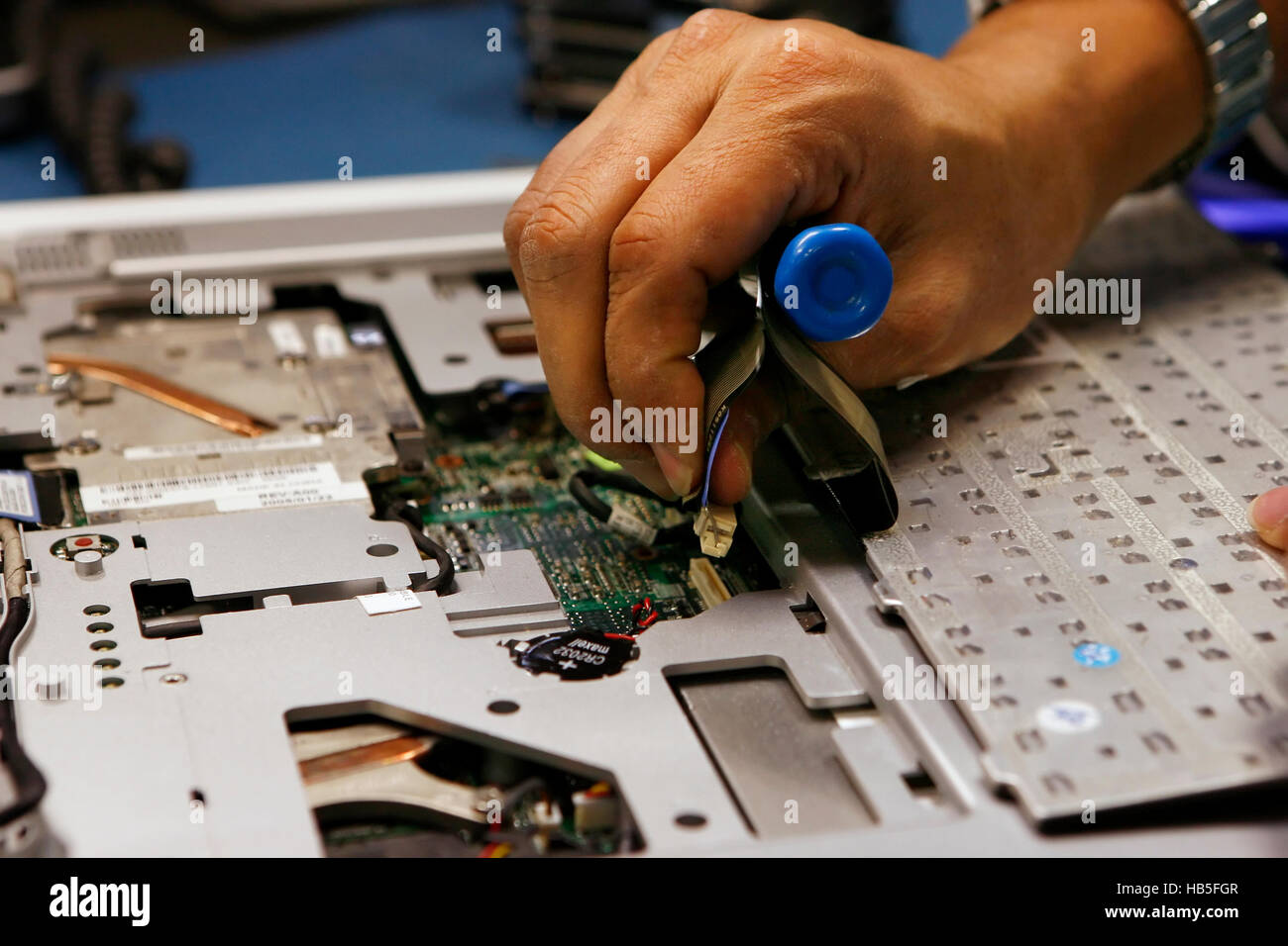 A worker at a computer recycling company in Austin, Texas takes apart a Dell laptop for recycling.  Photo by Erich Stock Photo