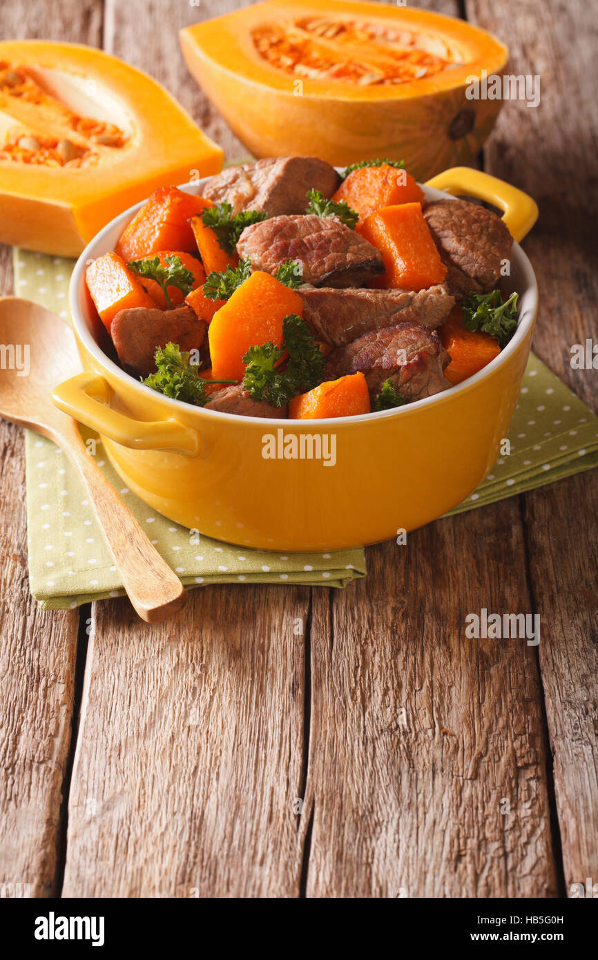 Beef stew with pumpkin, onion and spices close up in a yellow pan on the table. vertical - Stock Image