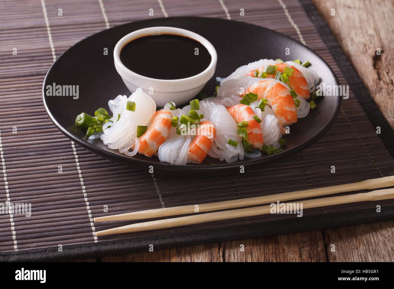 Japanese food: Shirataki with prawns, spring onions and soy sauce on a plate close-up. horizontal Stock Photo