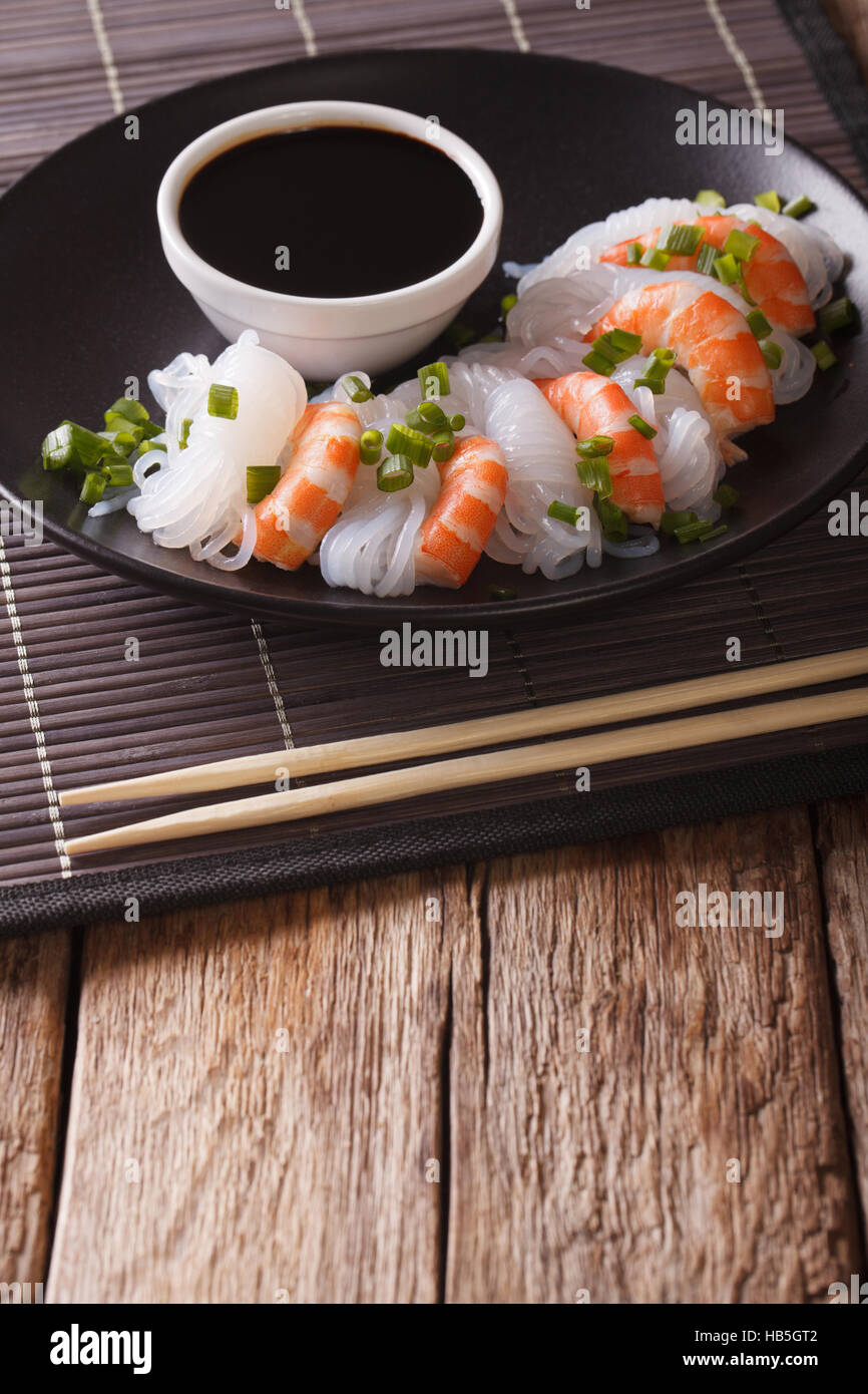 Japanese food: Shirataki with prawns, spring onions and soy sauce on a plate close-up. Vertical - Stock Image