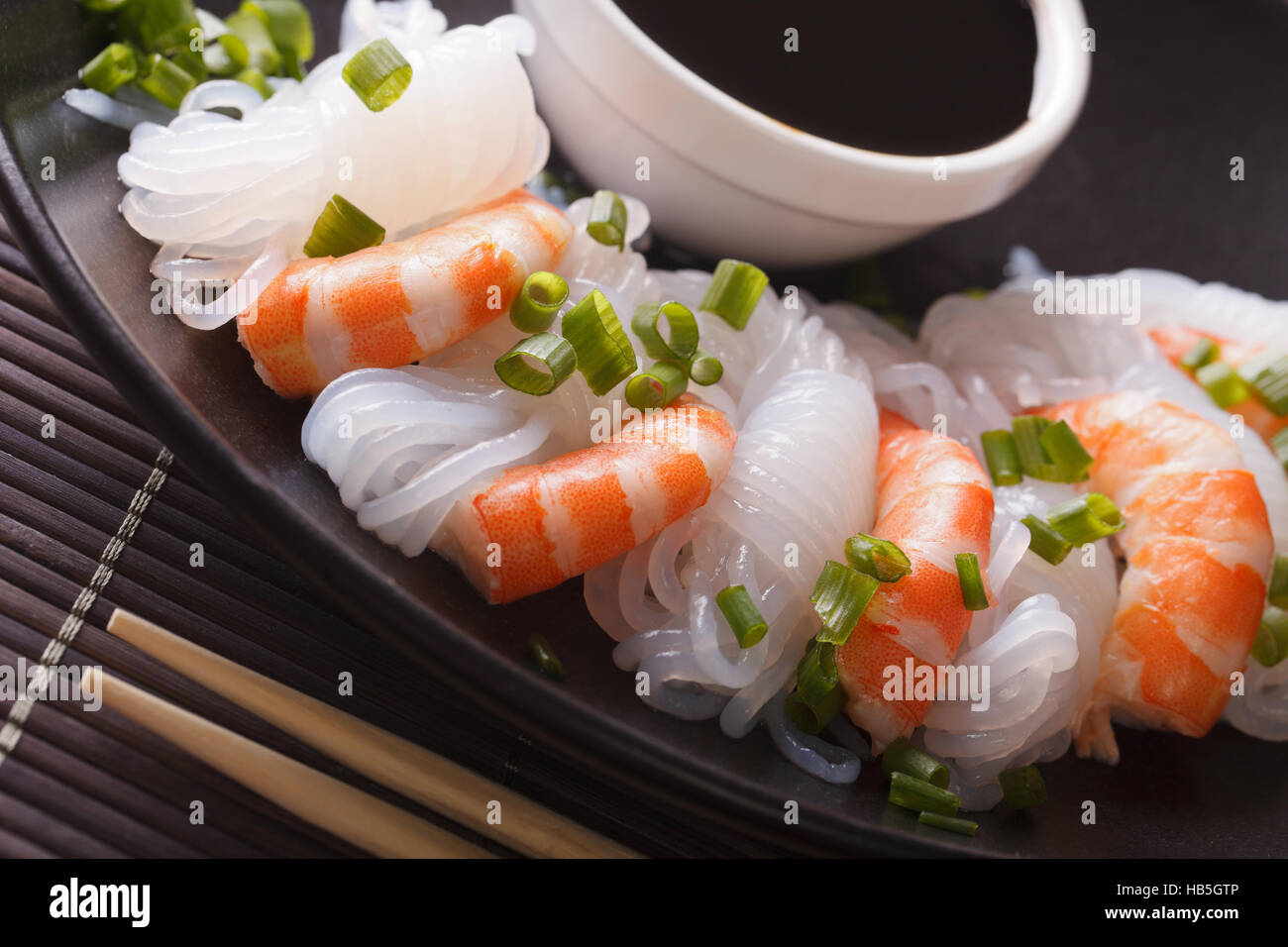 Shirataki with prawns, chives and soy sauce on a plate macro. horizontal - Stock Image