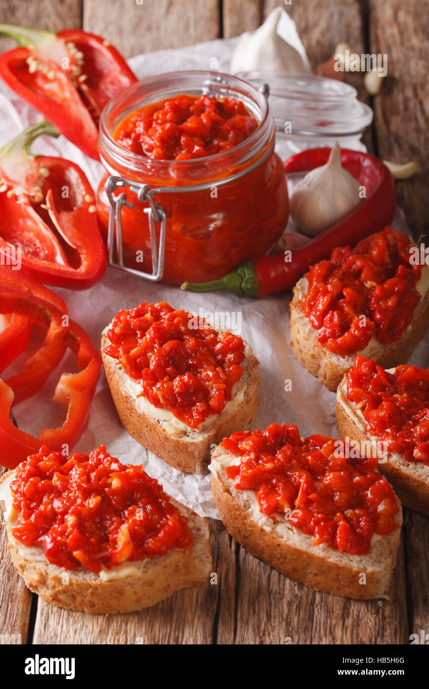 Relish (Ajvar) of Roasted Red Bell Peppers on toast slices close-up on the table. Vertical - Stock Image