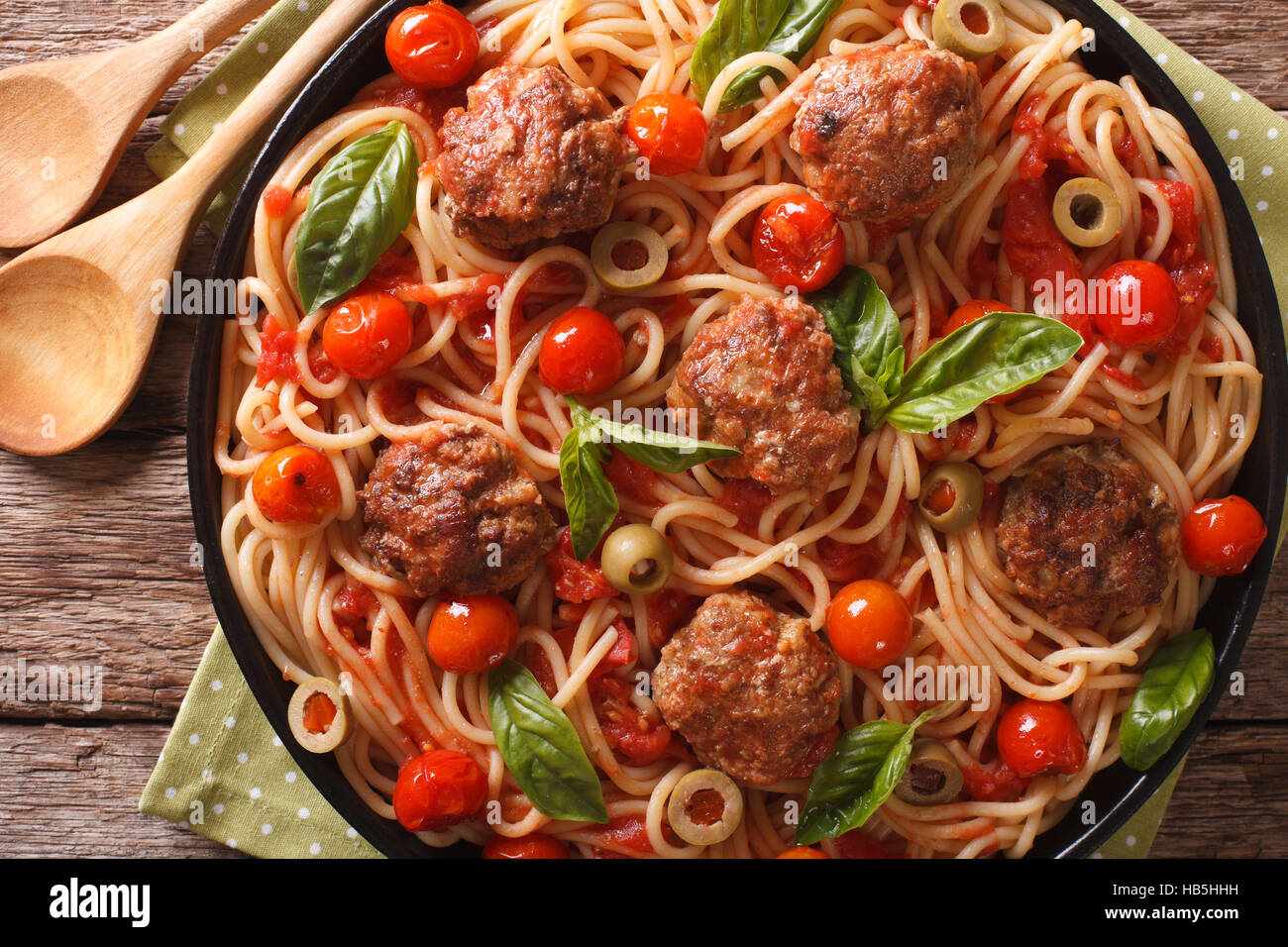 Italian food: spaghetti with meatballs, olives, basil and tomato sauce closeup on a plate. Horizontal view from - Stock Image