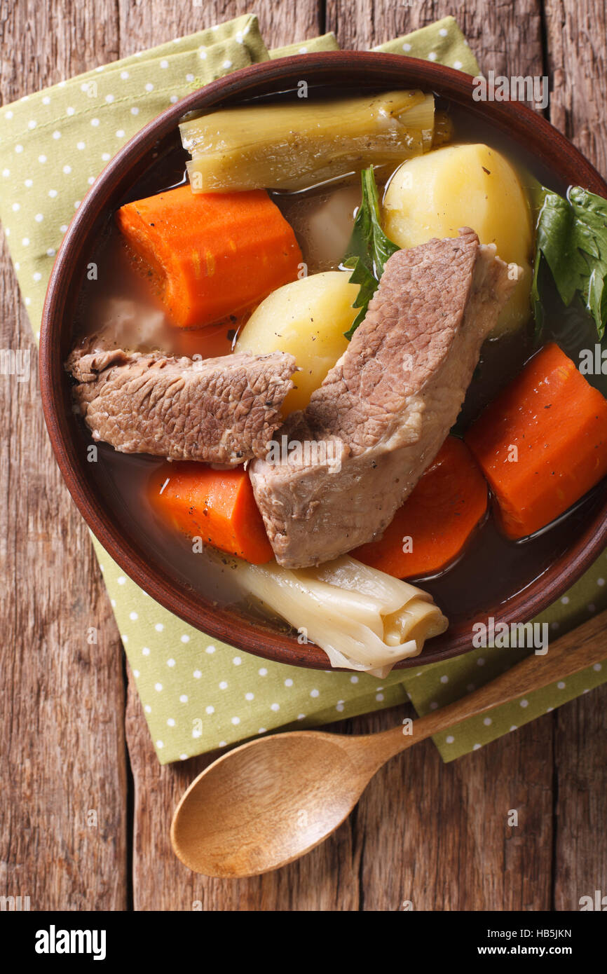 French Pot-au-feu soup closeup in a bowl on the table. Vertical view from above - Stock Image