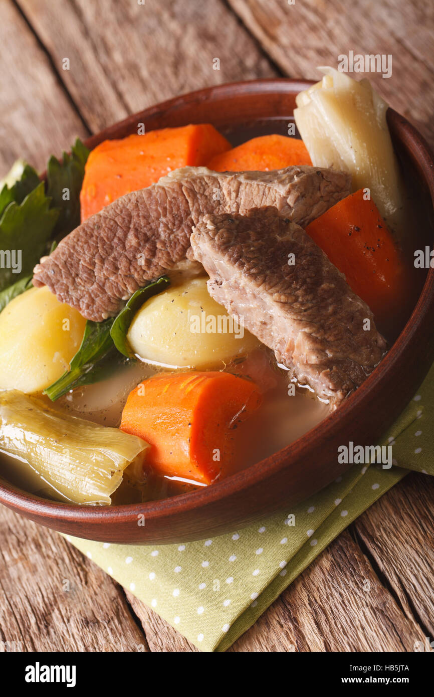 French cuisine Pot-au-feu soup close up in a bowl on the table. vertical - Stock Image