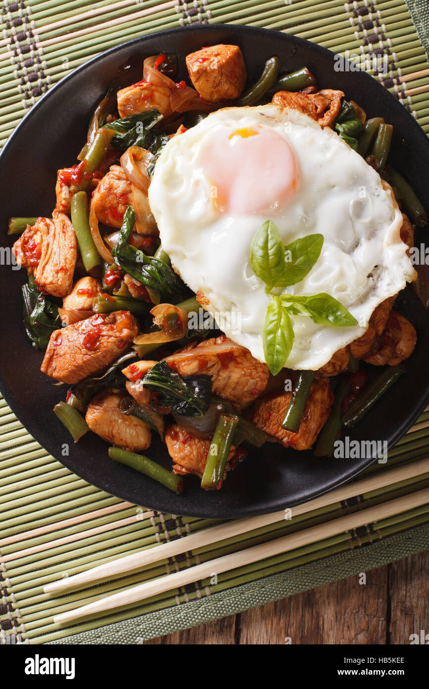 Stir-Fry Chicken with basil, green beans and a fried egg on a plate close-up. vertical view from above - Stock Image