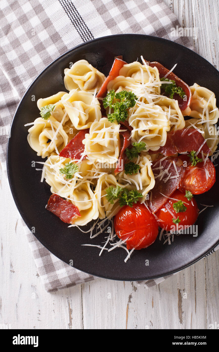 Italian tortellini with prosciutto, tomatoes and parmesan close-up on a plate. vertical view from above - Stock Image