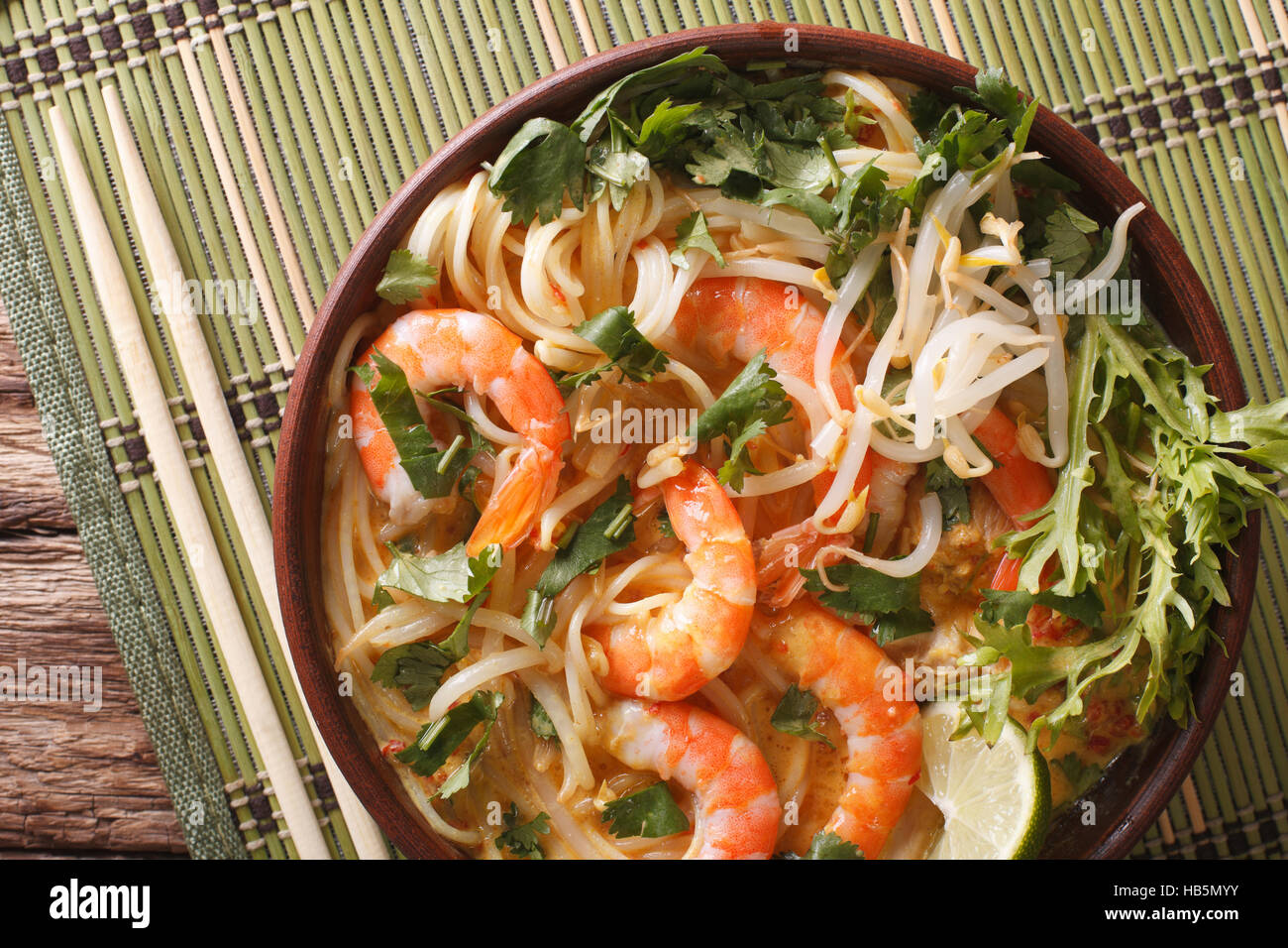 Malaysian laksa soup with prawns close up in a bowl on the table. horizontal view from above - Stock Image