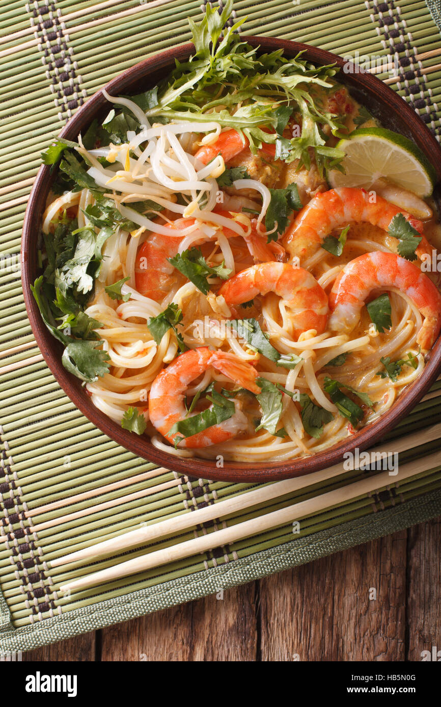 Malaysian laksa soup with prawns close up in a bowl on the table. vertical view from above - Stock Image