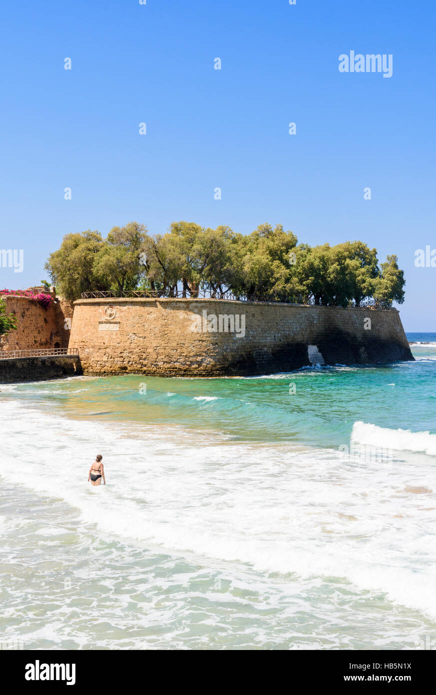 A woman walks into the sea near the Sabbionara Rampart part of the Venetian fortifications surrounding old Chania, - Stock Image