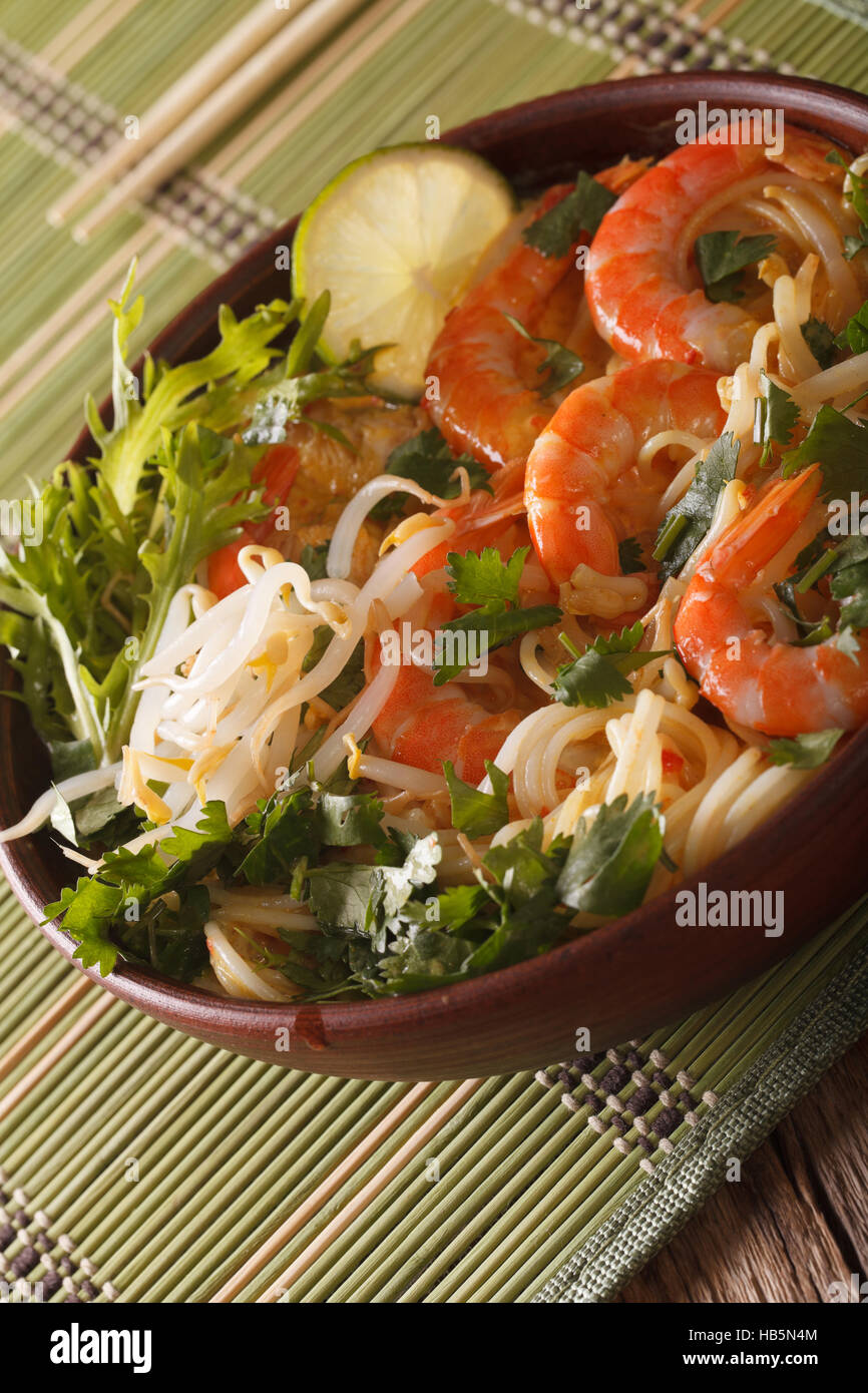 Malaysian laksa soup with prawns close up in a bowl on the table. Vertical - Stock Image