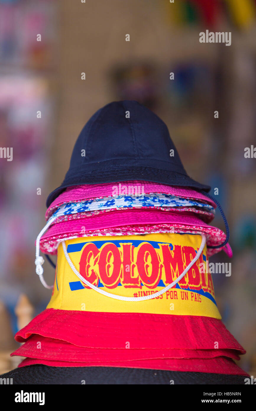 Top hats stacked with colombian letters colors in Guatape tourist market, Colombia - Stock Image