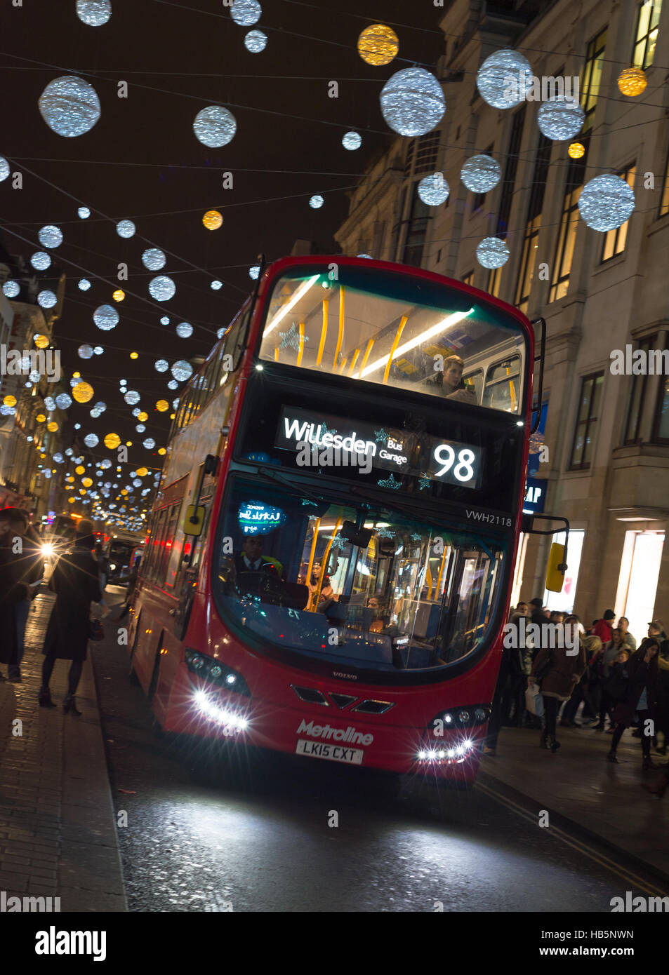 A 98 bus to Willesden navigates busy Oxford Street, London, during December's Christmas shopping spree. - Stock Image