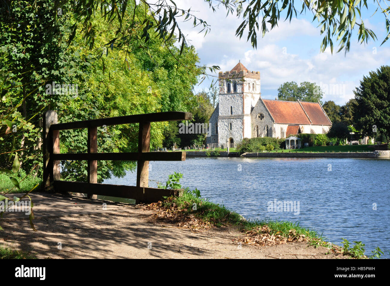 Bisham church -seen across the river from the Thames path - sunlight and shadows - an old footbridge - reflections - Stock Image