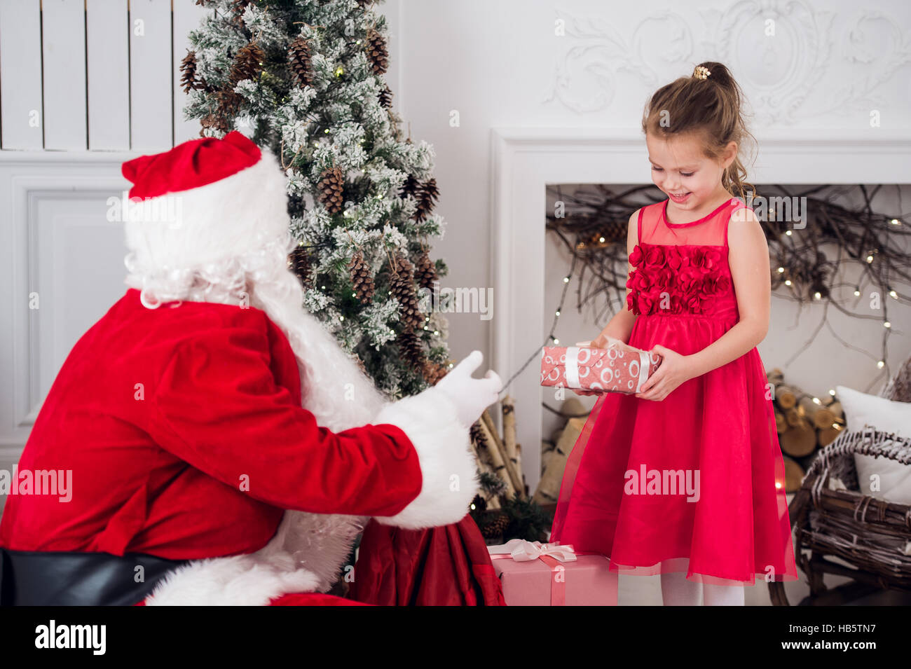 Santa Claus and children opening presents at fireplace. Kids father ...
