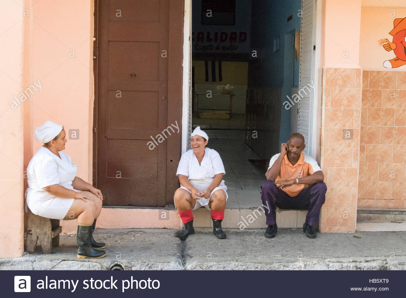 Cuban staff workers sitting and chatting merrily outside a building during their free time. - Stock Image
