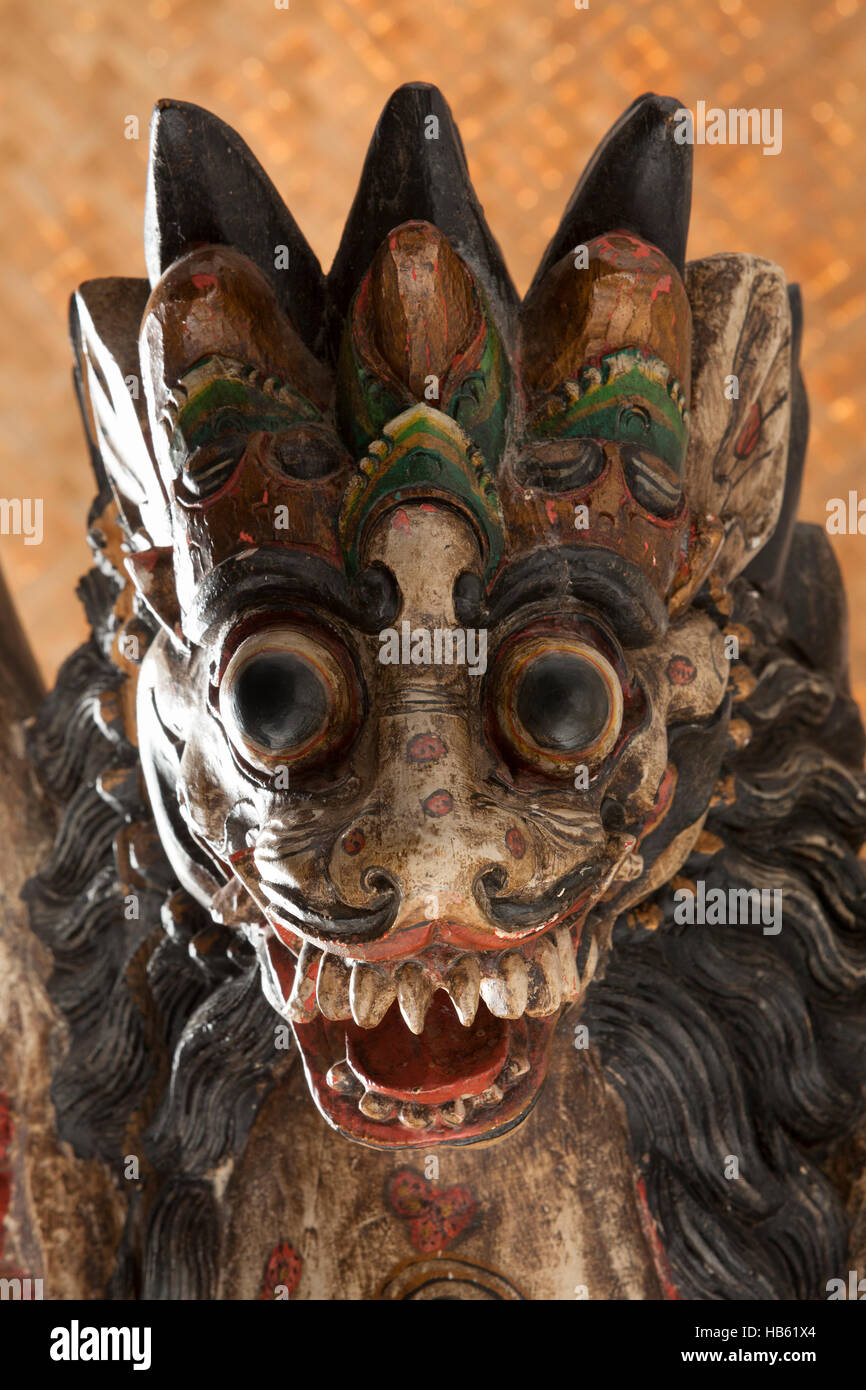 Head of an old wooden Balinese singha, a winged lion - Stock Image