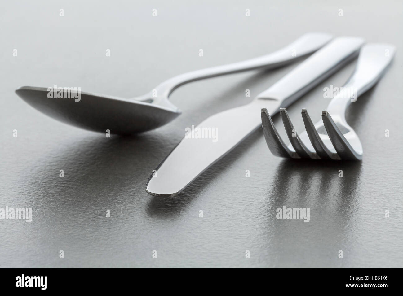 Shiny metal fork, knife and spoon - Stock Image