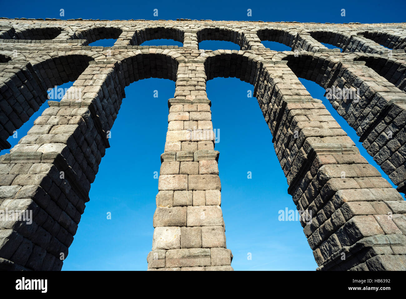 Looking up at Segovia's 1st century Roman Aqueduct in the Plaza Azuguejo, Segovia, Spain Stock Photo