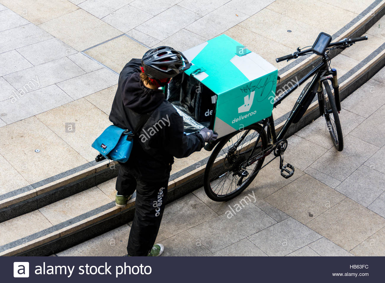 A Deliveroo delivery driver getting his delivery ready in London, UK - Stock Image
