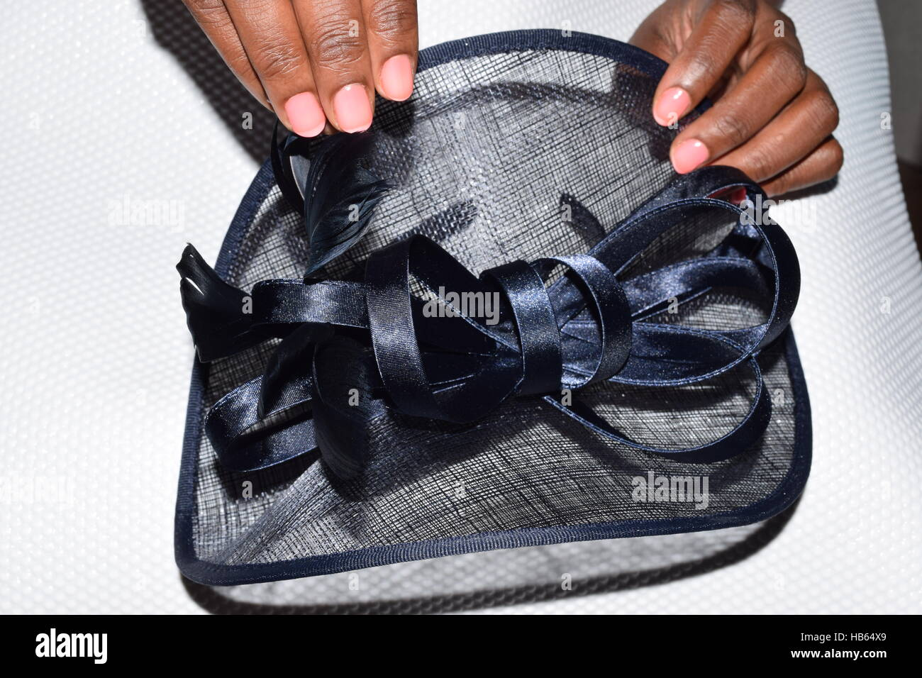 Black female hands holding a fancy navy blue hat with a small beautiful bow - Stock Image
