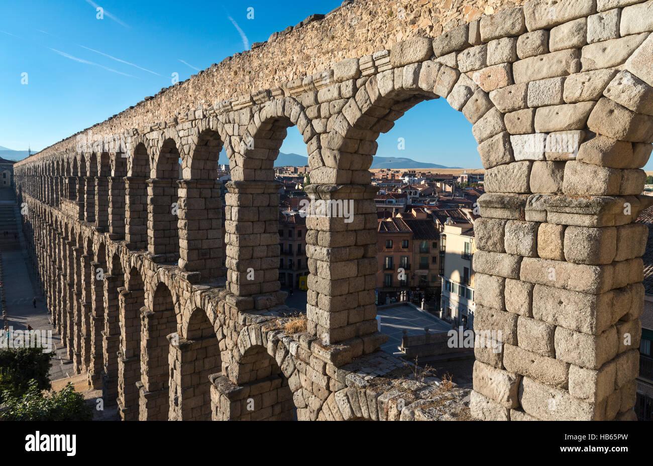 Looking along Segovia's 1st century Roman Aqueduct in the Plaza Azuguejo, Segovia, Spain Stock Photo