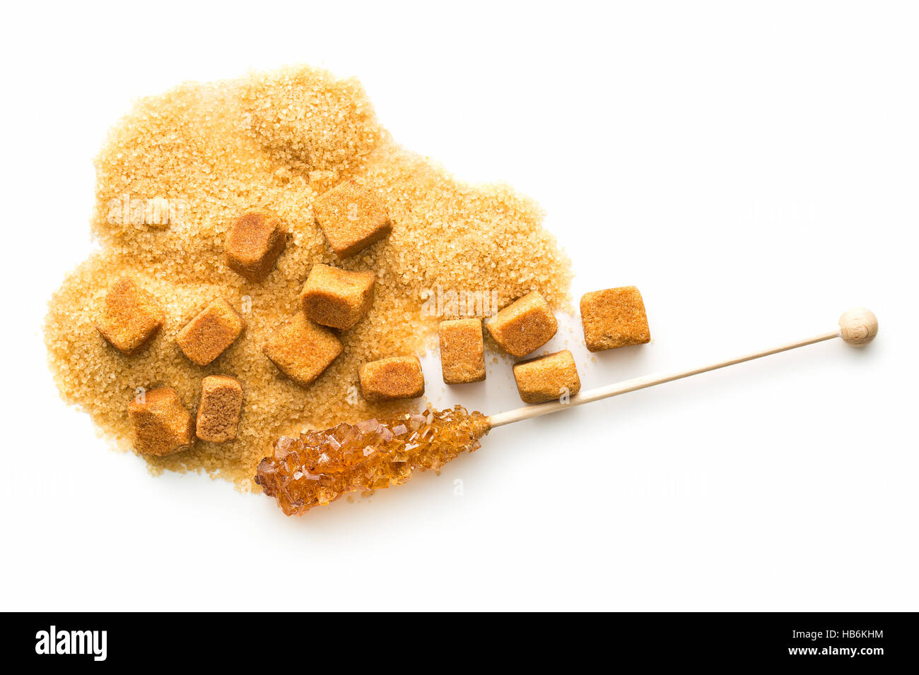 Brown amber sugar crystal on wooden stick and sugar cube isolated on white background. - Stock Image